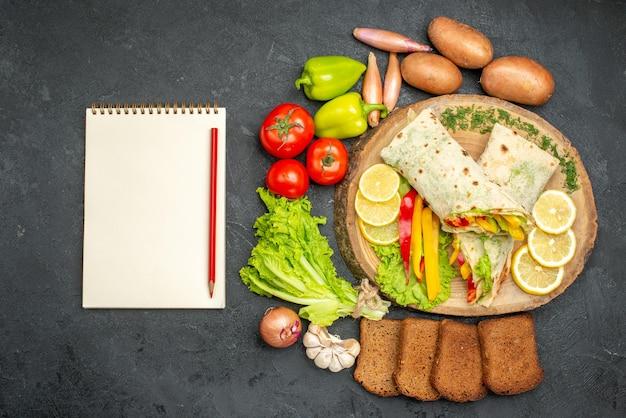 Vue de dessus d'un délicieux sandwich à la viande de shaurma en tranches avec du pain et des légumes sur fond noir
