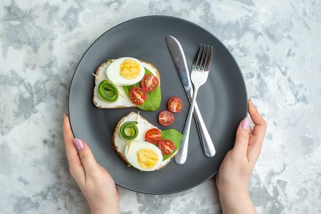Vue de dessus de délicieux sandwichs aux œufs avec couteau et fourchette à l'intérieur de la plaque fond blanc sandwich régime déjeuner toast alimentaire santé burger pain repas