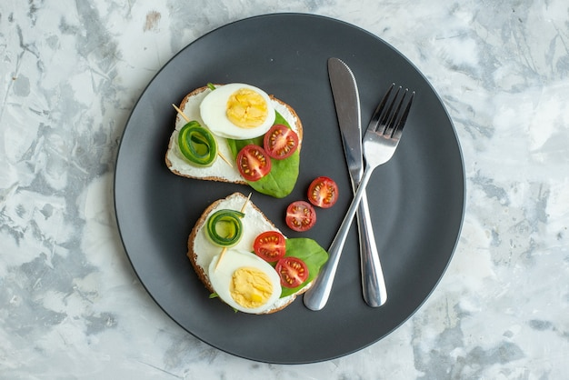 Vue de dessus de délicieux sandwichs aux œufs avec couteau et fourchette à l'intérieur de la plaque surface blanche sandwich régime repas santé déjeuner pain burger toast nourriture