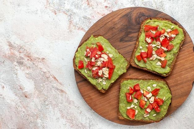 Vue de dessus de délicieux sandwichs à l'avocat avec des tranches de tomates rouges sur une surface blanche