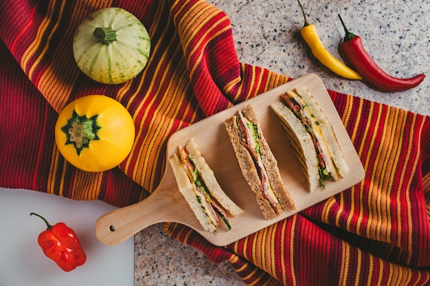 Vue de dessus de délicieux sandwichs en tranches avec jambon, fromage, herbes et légumes sur la table