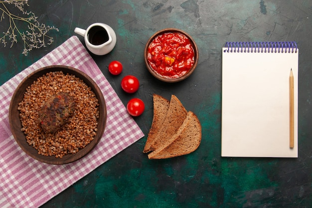 Vue de dessus délicieux sarrasin cuit avec des miches de pain et escalope sur la surface vert foncé ingrédient repas plat de légumes