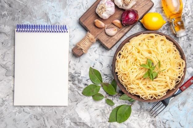 Vue de dessus de délicieux spaghettis à l'ail sur des pâtes de repas de pâte à dîner de table blanche
