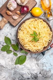 Vue de dessus de délicieux spaghettis à l'ail sur table blanche repas de pâte de pâtes poivre