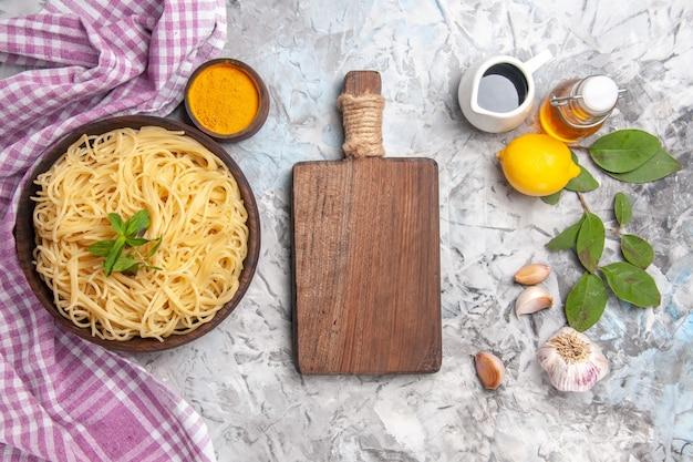 Vue de dessus de délicieux spaghettis aux assaisonnements sur la pâte de pâtes repas de table blanche