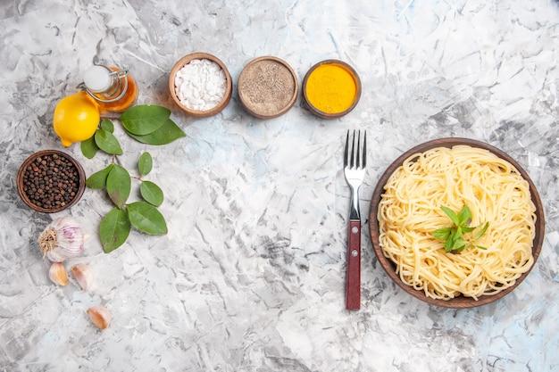 Vue de dessus de délicieux spaghettis aux assaisonnements sur des pâtes à pâte blanche