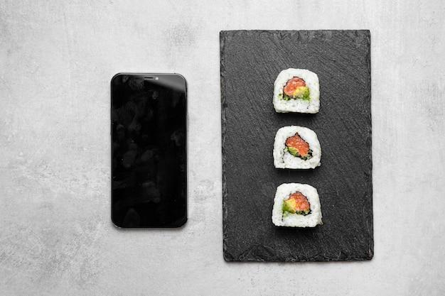 Vue de dessus de délicieux sushis et smartphone