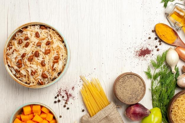 Vue de dessus de délicieux vermicelles cuits avec des haricots sur une table blanche
