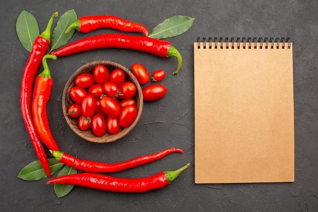 Vue de dessus demi-cercle de piments rouges et de feuilles de laurier et un bol de tomates cerises et un ordinateur portable sur le tableau noir