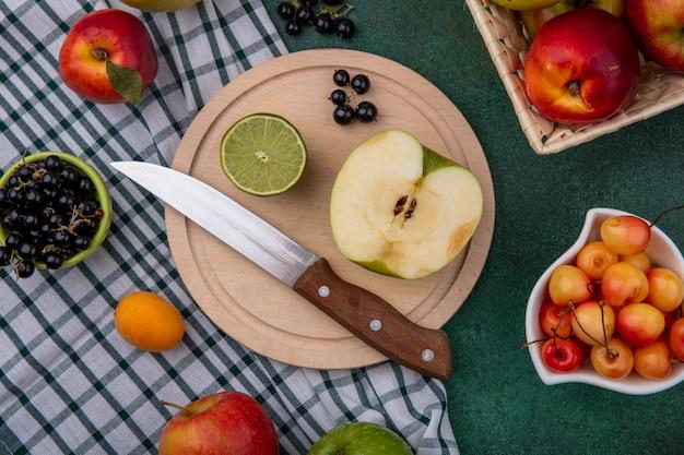 Vue de dessus d'une demi-pomme verte avec un couteau sur un support avec des cerises blanches à la chaux, cassis et pêches sur une serviette à carreaux sur une surface verte