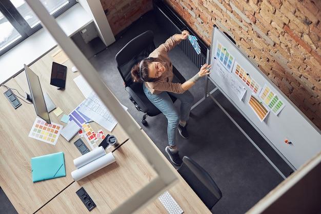 Vue de dessus d'une designer féminine moderne sélectionnant des couleurs à partir d'échantillons regardant un plan