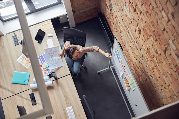 Vue de dessus d'une designer professionnelle portant des écouteurs attachant ou regardant des échantillons de couleurs
