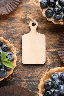 Vue de dessus des desserts aux myrtilles avec planche à découper