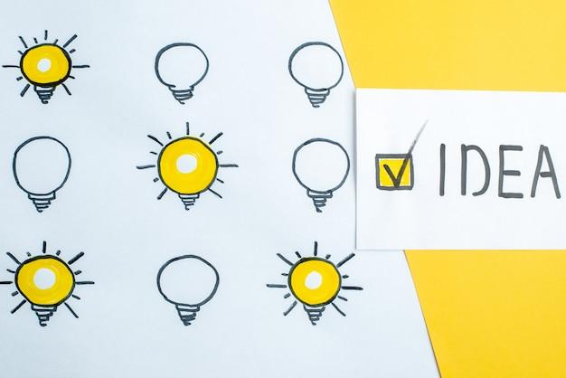 Vue de dessus des dessins de nombreuses ampoules éteintes éclairées idea écrit sur une petite feuille sur la moitié blanc moitié fond jaune