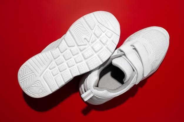 Vue de dessus deux baskets blanches pour enfants avec des bandes velcro avec des ombres solaires dures sur fond rouge une sne...