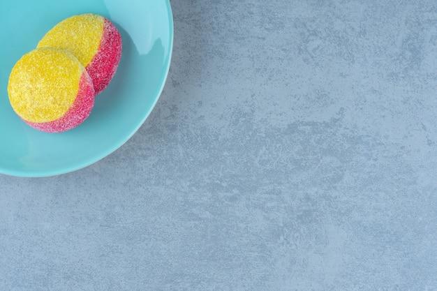 Vue de dessus de deux biscuits aux pêches sur plaque bleue.
