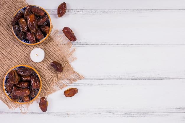 Une vue de dessus de deux bols avec des dates mûres juteuses sur une table boisée blanche