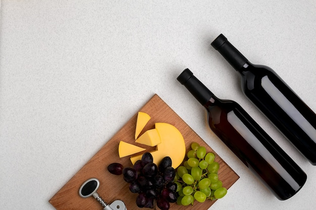Vue de dessus de deux bouteilles de vin blanc et rouge, fromage et raisins