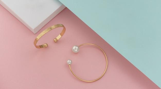 Vue de dessus de deux bracelets modernes sur papiers de couleurs pastel
