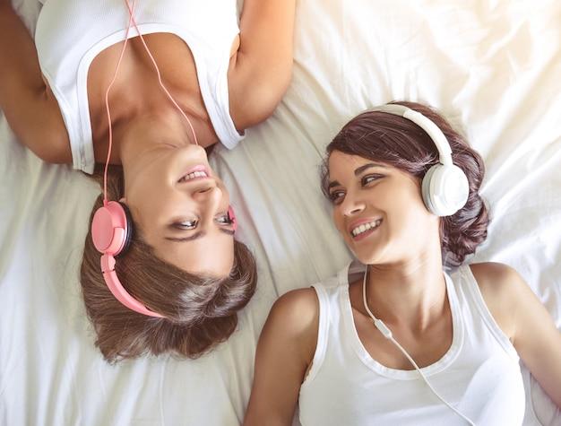 Vue de dessus de deux filles dans les écouteurs en écoutant de la musique.