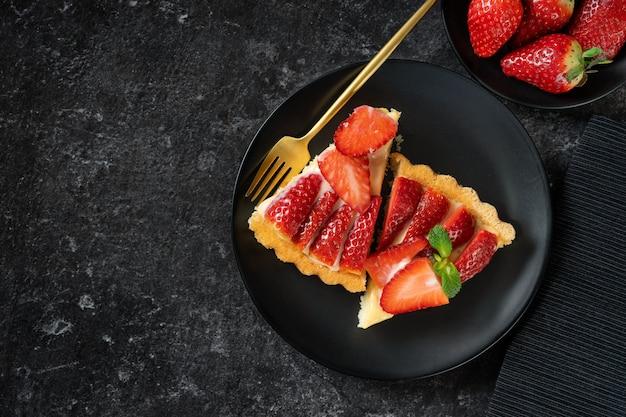 Vue de dessus de deux galettes de gâteau aux fraises sur fond noir
