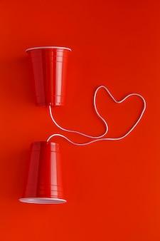 Vue de dessus de deux gobelets en papier avec de la ficelle pour parler