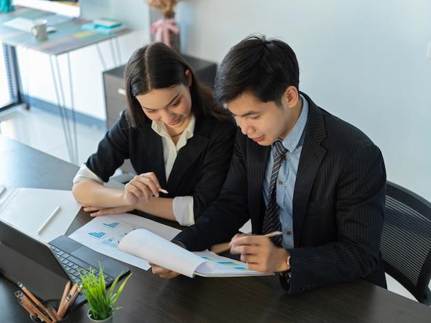 Vue de dessus de deux hommes d'affaires consultant sur leur stratégie commerciale dans la salle de réunion