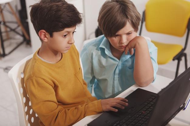 Vue de dessus de deux jeunes garçons utilisant un ordinateur portable ensemble
