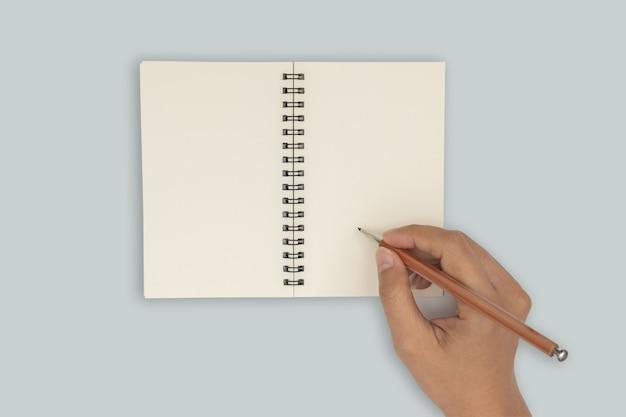 Vue de dessus - deux mains tiennent un livre vide étalé et écrivant un cahier