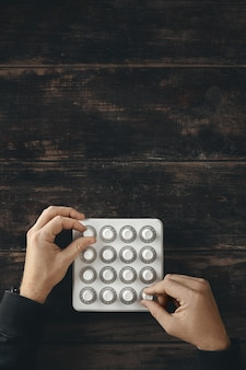 Vue de dessus, deux mains tournent avec précision les boutons sur le contrôle du mélangeur midi sans fil