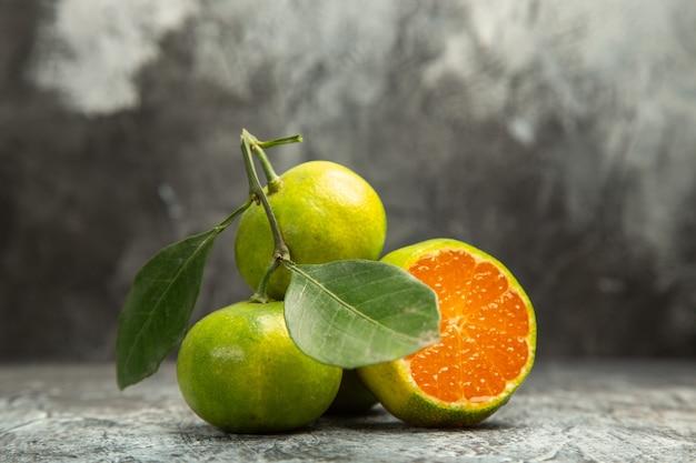 Vue de dessus de deux mandarines vertes entières fraîches avec des feuilles et une mandarine coupée en deux sur des images de fond gris
