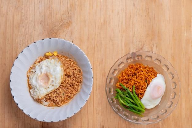 Vue de dessus de deux nouilles aux œufs et aux asperges sur fond de table en bois avec espace de copie