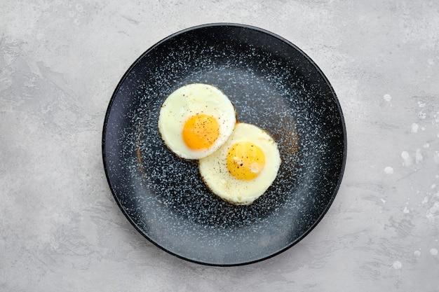 Vue de dessus de deux œufs au plat sur une assiette