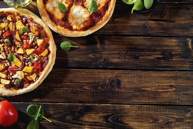 Vue de dessus de deux pizzas végétaliennes sur fond rustique foncé