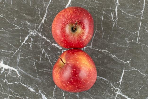 Vue de dessus de deux pommes fraîches sur pierre grise.
