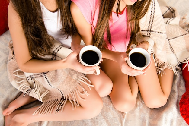 Vue de dessus de deux soeurs sexy buvant du café au lit