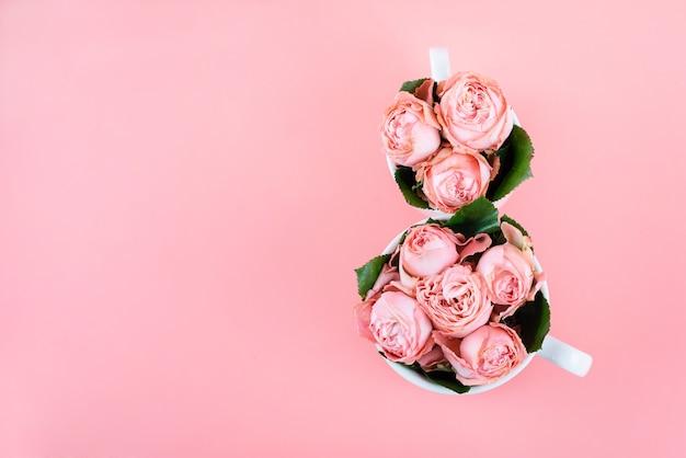 Vue de dessus avec deux tasses de café avec des fleurs roses de l'espace de copie. contexte de la journée de la femme du 8 mars.