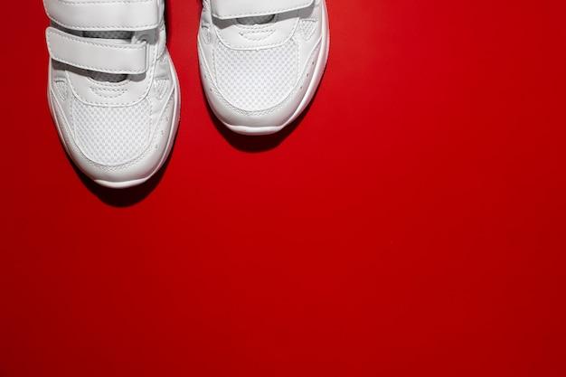 Vue de dessus sur le devant de deux baskets de sport blanches dans le coin avec un espace de copie isolé sur un dos rouge...