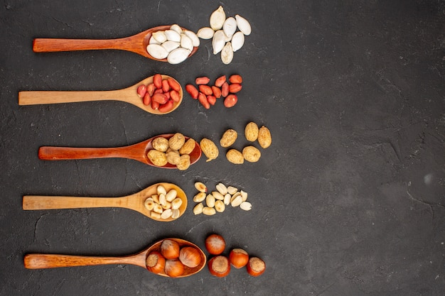 Vue de dessus de différentes arachides de noix fraîches et autres noix sur une surface sombre