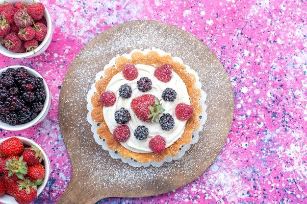 Vue de dessus de différentes baies fraîches à l'intérieur de tasses blanches avec un gâteau sur la lumière, les petits fruits frais aigre