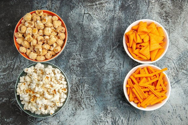 Vue de dessus différentes biscottes et cips de pop-corn sur une surface légère