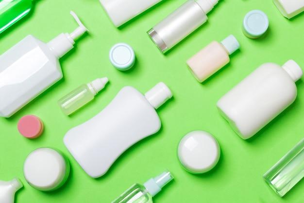 Vue de dessus de différentes bouteilles cosmétiques et conteneurs pour cosmétiques sur fond vert. composition à plat avec espace de copie.