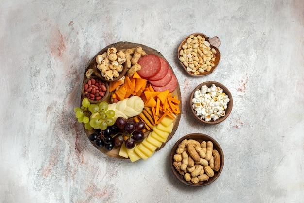 Vue de dessus différentes collations noix cips fromage et saucisses sur fond blanc snack-repas alimentaire