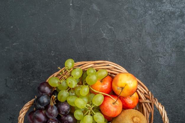 Vue de dessus différentes compositions de fruits frais et mûrs à l'intérieur du panier sur le fond gris foncé fruits frais moelleux santé mûrs