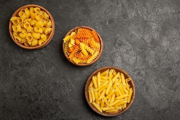 Vue de dessus de différentes compositions de pâtes produit brut à l'intérieur des assiettes sur la cuisson des repas de pâte crue de pâtes grises