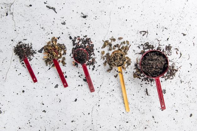 Vue de dessus sur différentes cuillères de mesure avec du thé noir sur fond blanc