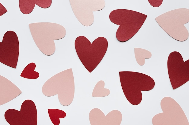 Vue de dessus différentes formes de coeur rouge et rose sur table