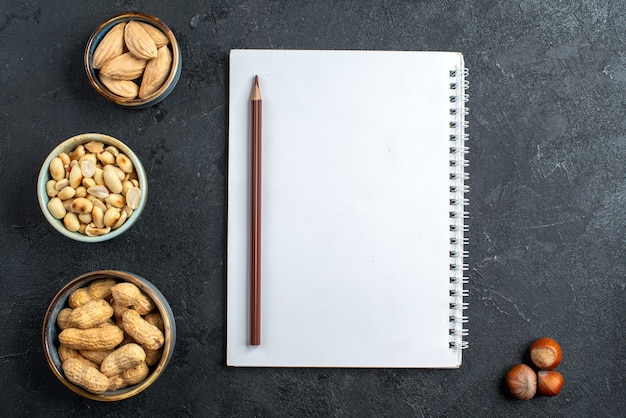 Vue de dessus différentes noix avec bloc-notes sur fond gris snack noix raisin sec noix de fruits secs