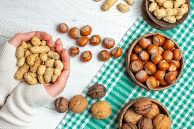 Vue de dessus différentes noix cacahuètes noisettes et noix sur un tableau blanc dans une main féminine
