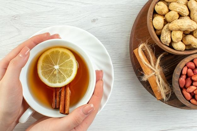 Vue de dessus différentes noix cacahuètes noisettes et noix avec une tasse de thé sur un tableau blanc